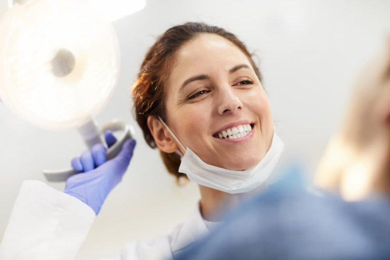 happy-dentist-looking-at-patient-EH54GLD (1)