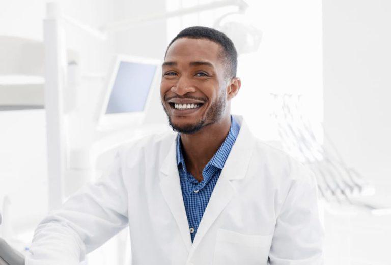 handsome-black-dentist-smiling-over-modern-dental--833H986 (1)